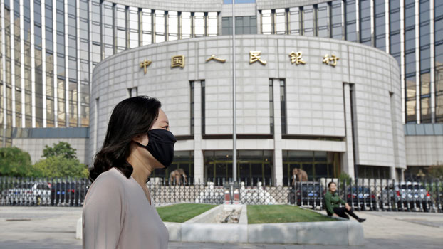 A woman wearing a face mask walks past the headquarters of the People's Bank of China (PBOC), the central bank, in Beijing, Sept. 28, 2018.