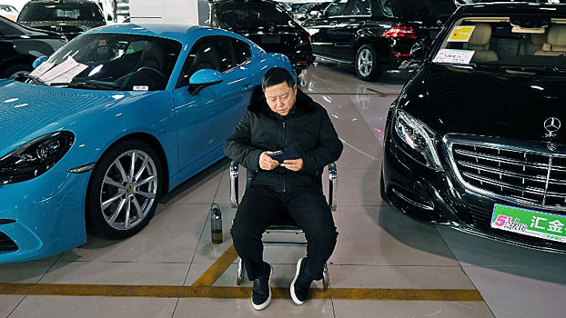 A sales representative waits for customers in a luxury car showroom in Beijing, Jan. 22, 2019.