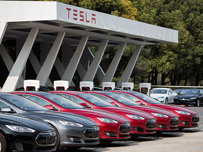 Tesla Model S electric vehicles are parked outside a car dealership in Shanghai, March 17, 2015.