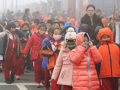 Chinese elementary school students cover their mouths and noses as they leave the schoolyard after classes were suspended because of a 'red alert' for heavy smog in Binzhou, eastern China's Shandong province, Dec. 23, 2015.