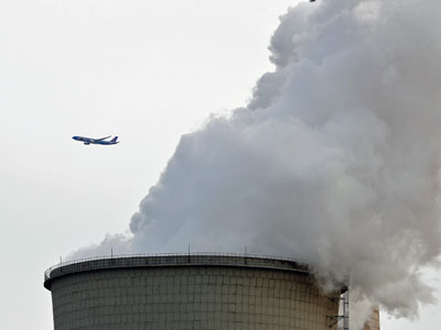 A passenger jet flies past steam and white smoke emitted by a coal-fired power plant in Beijing, China, Feb. 28, 2017.