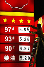 A Chinese petrol station worker changes the fuel pricing on a board at a station in the southwest municipality of Chongqing early 01 November 2007. Photo: AFP