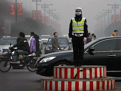 A traffic police officer wearing a face mask directs vehicles on a road in heavy smog in Xi'an, northern China's Shaanxi province, Feb. 2, 2014.