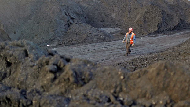 A worker walks past coal piles at a coal coking plant in Yuncheng, northern China's Shanxi province, Jan. 31, 2018.