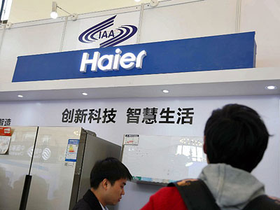 Chinese visitors look at electric home appliances manufactured by Haier Group at an expo in Shanghai, Nov. 27, 2015.