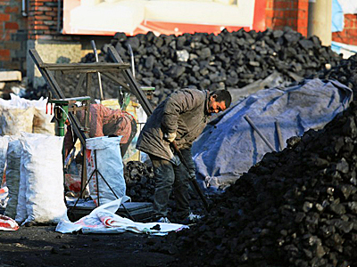 A Chinese worker levels coal at a coal yard in Jinhu county, east China's Jiangsu province, Feb. 2, 2016.