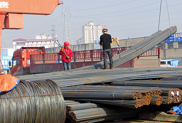 230400b83b2 Chinese workers move a bundle of reinforcing steel rods at a steel product  market in Yichang
