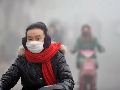 A woman rides a bike in heavy smog along a street in Haozhou, central China's Anhui province, Jan. 30, 2013.