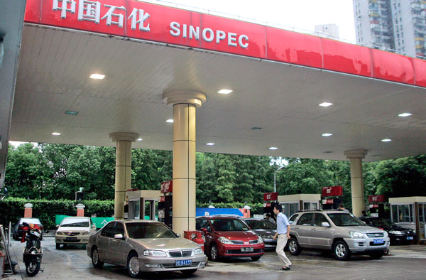 Customers fill up at a Sinopec gas station in Shanghai, China, in a file photo.