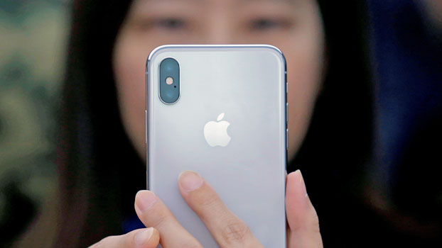 A Chinese woman uses a new iPhone X during a presentation for the media in Beijing, Oct. 31, 2017.