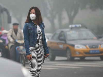 A Chinese pedestrian wearing a face mask walks on a road in heavy smog in Beijing, Oct. 14, 2016.