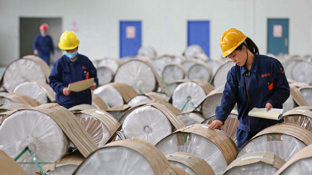 Chinese workers check rolls of sheet aluminum at a factory in Huaibei, eastern China's Anhui province, April 25, 2019.