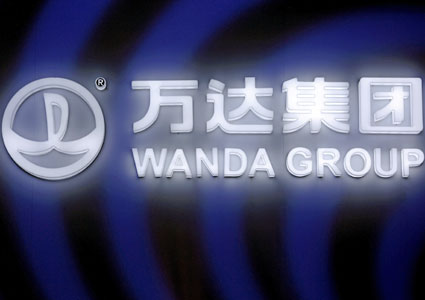 A Dalian Wanda Group sign glows during an event announcing a strategic partnership between Wanda Group and FIFA in Beijing, China, March 21, 2016.