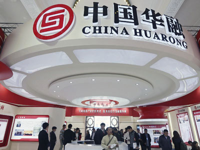 Attendees at a finance expo pass by the booth of China Huarong Asset Management Company Ltd. in Beijing, Oct. 30, 2014.
