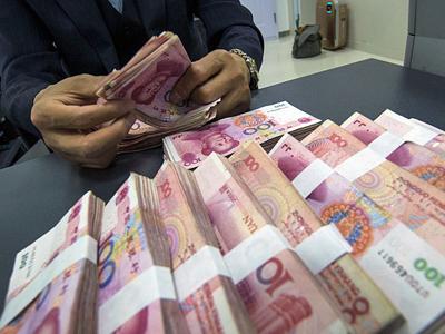 A Chinese clerk counts renminbi yuan banknotes at a bank in Nantong, east China's Jiangsu province, May 23, 2016.