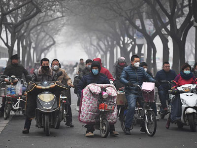 Scooter riders wait to cross a road on a heavily polluted day in Shijiazhuang, northern China's Hebei province, Dec. 21, 2016.