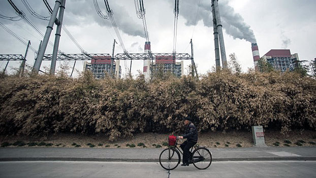 A man rides a bike past a coal-fired power plant operated by China's Shanghai Waigaoqiao Electric Power Generating Company Ltd. in Shanghai, March 22, 2016.