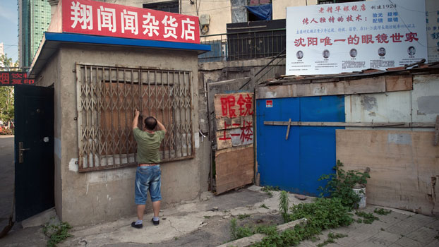A Chinese man closes his small shop in Shenyang, northeastern China's Liaoning province, July 4, 2017.