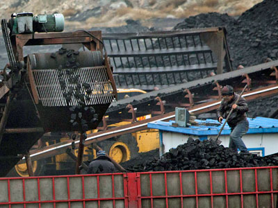 Chinese workers shovel coal as a conveyor loads it into a trailer truck at a coal mine near Ordos in northern China's Inner Mongolia Autonomous Region, Nov. 3, 2015.