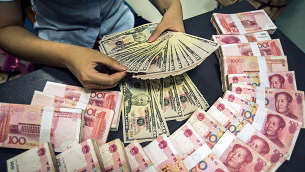 A Chinese Clerk Counts U S Dollar Banknotes Next To Yuan Renminbi Bills At Bank In