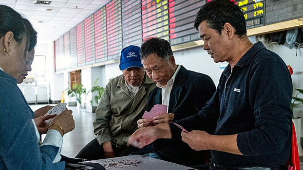 Chinese investors play cards in front of an electronic board showing stock information at a brokerage firm in Shanghai, Oct. 15, 2018.