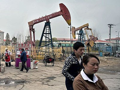 Chinese locals walk beside oil pumps in Daqing, northeastern China's Heilongjiang province, May 2, 2016.