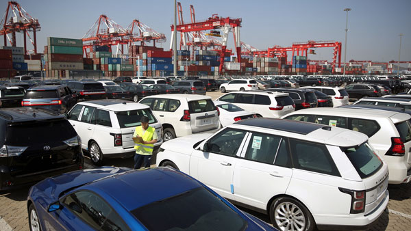 A worker inspects imported cars at a port in Qingdao, eastern China's Shandong province, May 23, 2018.