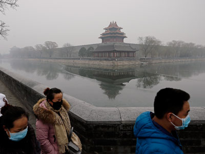Chinese people wearing masks for protection against pollution walk past the turret of the Forbidden City on a heavily polluted day in Beijing, Dec. 8, 2015.