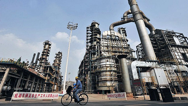 A worker rides a bicycle at a Sinopec oil refinery in Wuhan, central China's Hubei province, in a file photo.