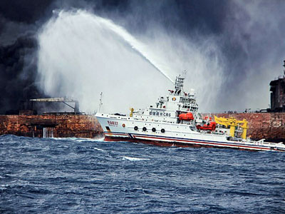A Chinese firefighting vessel sprays foam on the burning oil tanker Sanchi at sea off the coast of eastern China, Jan. 12, 2018.