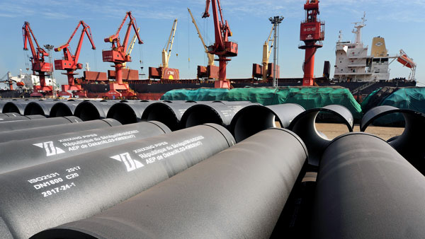 Cranes prepare to load steel pipes for export at a port in Lianyungang in coastal China's Jiangsu province, May 31, 2018.