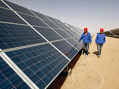Chinese workers walk past arrays of solar panels at a solar power plant in northwestern China's Qinghai province in a file photo.