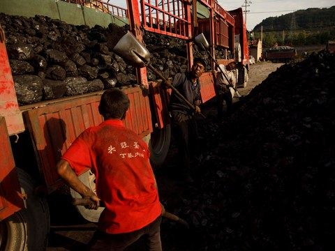 Workers shovel coal onto a truck at a coal yard near a coal mine in Huating, Gansu province, China, September 18, 2020.