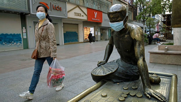 A woman passes a bronze statue covered with a face mask on a partially closed retail street in Wuhan, central China's Hubei province, April 13, 2020.