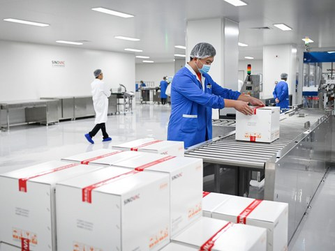 A staff member works during a media tour of a new factory built to produce a COVID-19 coronavirus vaccine at Sinovac, one of 11 Chinese companies approved to carry out clinical trials of potential coronavirus vaccines, in Beijing on September 24, 2020.