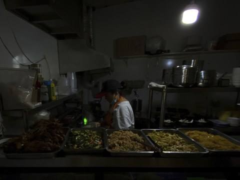 A woman uses a light bulb powered by portable battery as she prepares dishes in an earlier morning at a restaurant during a blackout in Shenyang in northeastern China's Liaoning Province, Wednesday, Sept. 29, 2021.