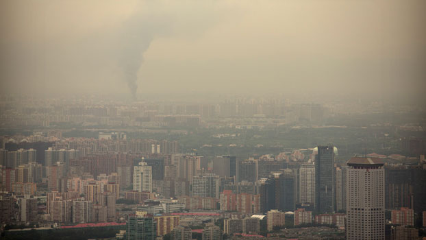 Smoke rises above the skyline of Beijing on a moderately polluted day, Aug. 26, 2017.