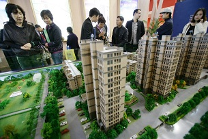 Chinese home buyers look at models of an apartment project at a real estate fair in Ningbo, Nov. 2, 2012.
