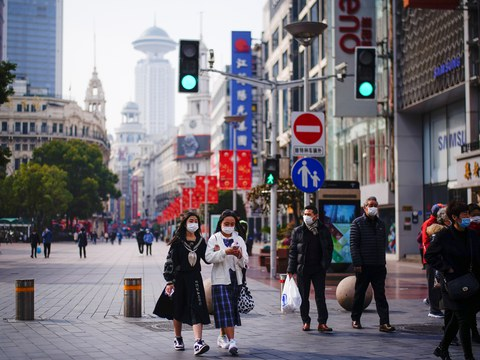 People wearing face masks walk at a main shopping area, following the coronavirus disease (COVID-19) outbreak in Shanghai, China January 27, 2021.