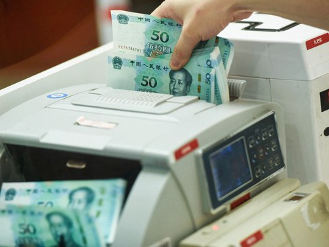 A Chinese bank employee counts new 50-yuan notes with a money counting machine at a bank counter in Hangzhou in China's eastern Zhejiang province on August 30, 2019