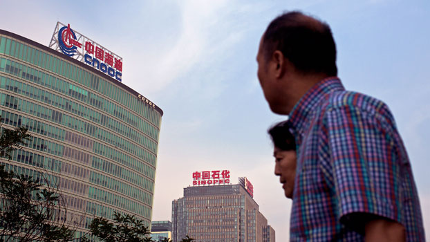 People walk past the headquarters of China National Offshore Oil Corp. (L) and China Petroleum & Chemical Corp. (Sinopec) (C) in Beijing, Sept. 14, 2015.