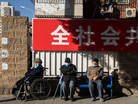 Elderly people sit in a street during morning rush hour in Beijing, China, November 3, 2020.