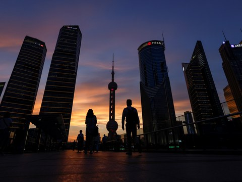People walk in Lujiazui financial district during sunset in Pudong, Shanghai, China July 13, 2021.