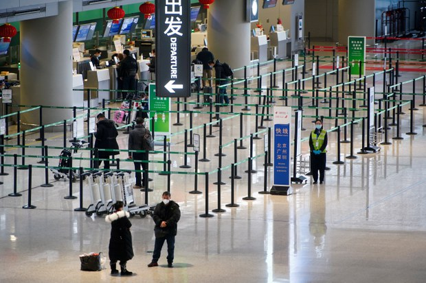 Travellers wearing face masks following the coronavirus disease (COVID-19) outbreak wait at check-in counters of Shanghai Hongqiao International Airport as the Spring Festival travel season begins ahead of the Chinese Lunar New Year, in Shanghai, China, January 28, 2021.