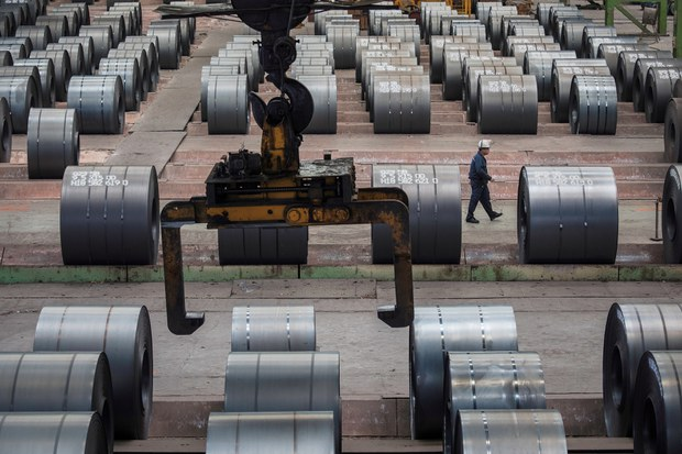 A worker walks past steel rolls at the Chongqing Iron and Steel plant in Changshou, Chongqing, China August 6, 2018. Picture taken August 6, 2018.