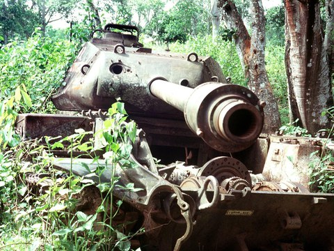 A destroyed tank sits in overgrown woods along the Ho Chi Minh Trail in Laos in a file photo.