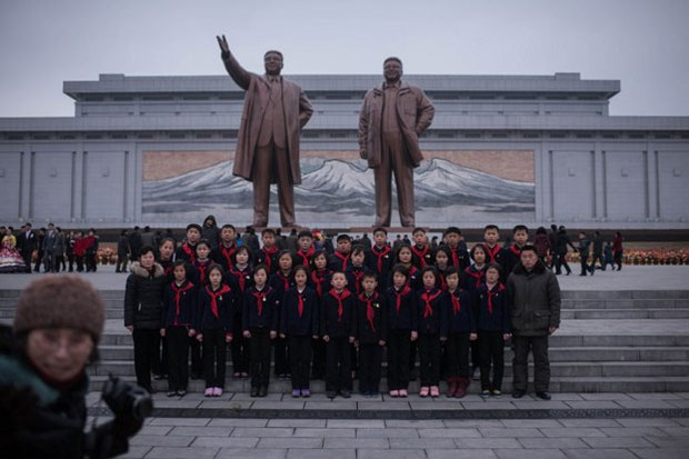 A group of children pose for a group photo under the statues of late North Korean leaders Kim Il Sung and Kim Jong Il on the 75th anniversary of the birth of Kim Jong Il, at Mansudae hill in Pyongyang, Feb. 16, 2017.