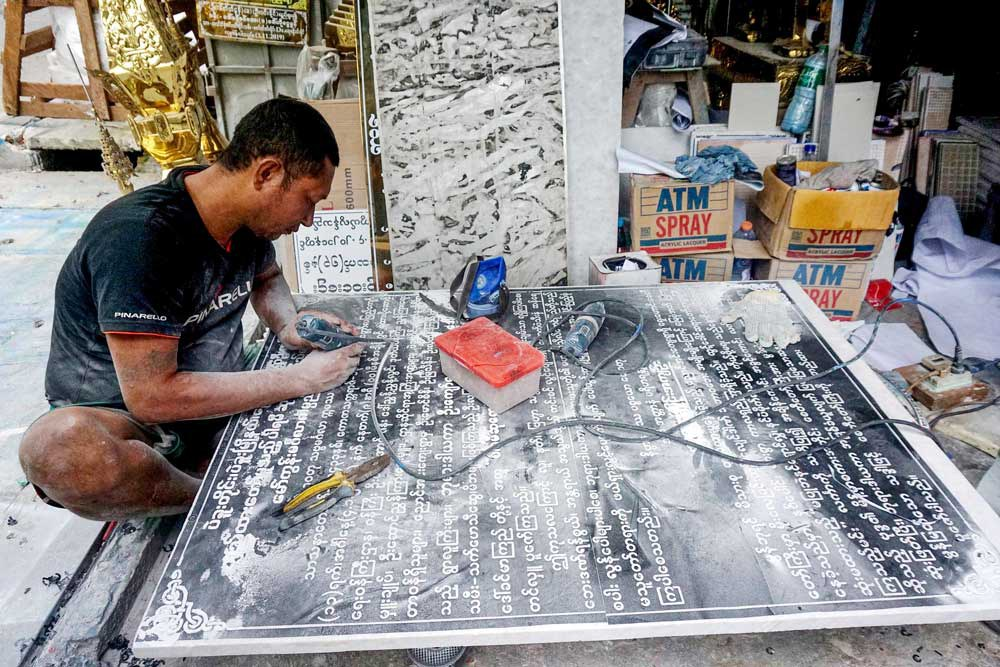 A craftsman inscribes names, donations and wishes on a marble slab for a pagoda. Inscriptions used to take a week but now can be done in a day using digitized fonts on a computer. (Myo Min Soe/RFA)