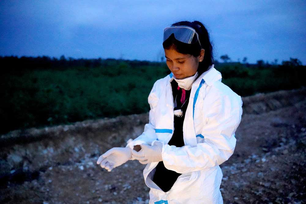 """Thavry Hoem, a field study coordinator at the IPC, puts on personal protective equipment before collecting bats. """"We hope that the result from this study can help the world to have a better understanding about COVID-19,"""" she told Reuters. (Reuters)"""