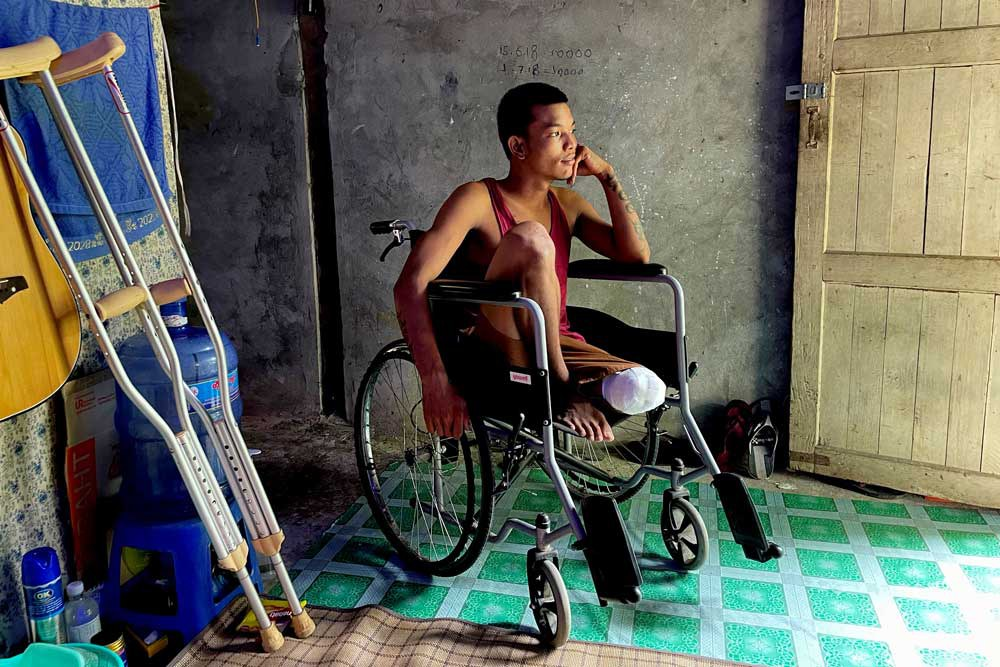 """Ko Phyo, 24, sits in his wheelchair at his home on the outskirts of Yangon, Myanmar. He says the soldier who shot him removed the bullet with a knife and a policeman he knew took him to a military hospital. """"I started feeling the pain, and I couldn't bear it. I told them to cut off my leg immediately. They cut it on the seventh day."""" (REUTERS)"""